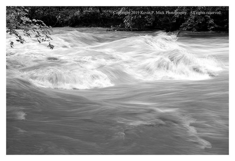 BW photograph of turbulence caused by floodwaters flowing over rocks.