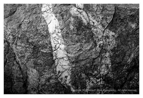 BW photograph of a line of quartz running through a larger rock.