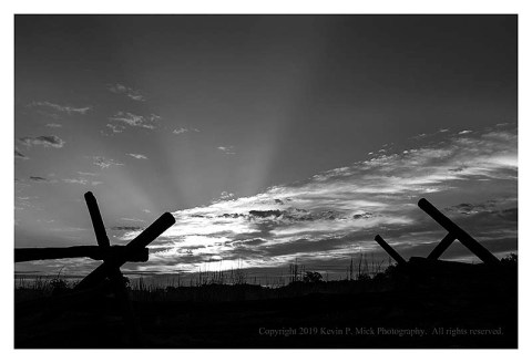 BW photograph of a sunrise behind a split rail fence at Gettysburg.