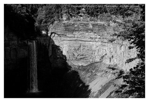 BW photograph of Taugahannock Falls canyon under strong sidelight-the falls are in shadow while the canyon wall is strongly lit.