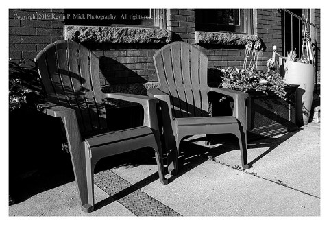 BW photograph of two chairs sitting on the sidewalk on an early, hot, summer morning.