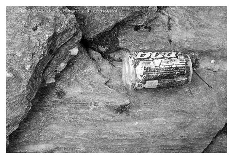 BW photograph of a dented beer car atop a large rock.