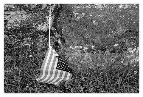 BW photograph of a United States flag torn from its stick and laying on the ground next to a large rock.