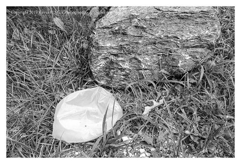 BW photograph of a crushed plastic gallon jug next to a large rock.