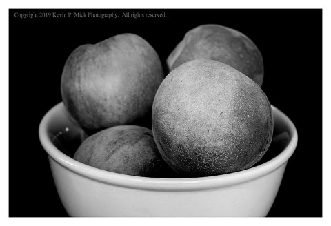 BW photograph of a bowl of fresh peaches.