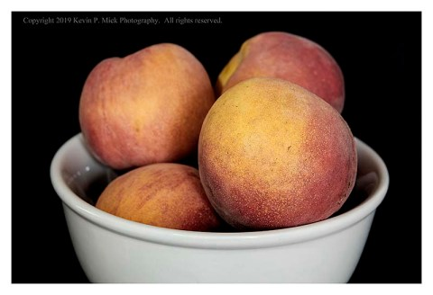 Colour photograph of a bowl of fresh peaches.