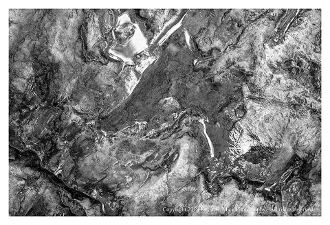 BW photograph of a small rain puddle atop a large rock.