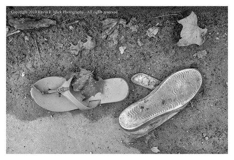 BW photograph of a left behind sandle and shoe amid leafy debris.