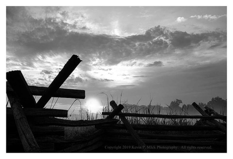 BW photograph of the sun rising behind a split rail fence.