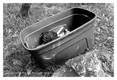 BW photograph of a large plastic bin filled with trash that was left behind.