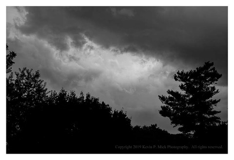 BW photograph of active thunderstorm clouds with silhouetted trees.