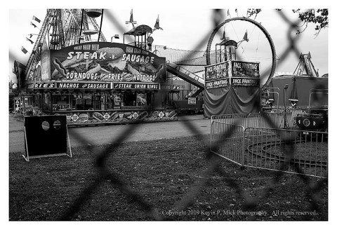 BW photograph of a food stand at a fair as seen through a chain link fence.