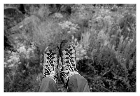 BW photograph of a pair of feet in boots hanging over the side of a large boulder.