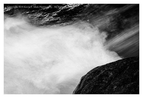 BW photograph of water rushing between rocks.