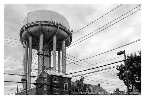 BW photograph of a water tower with the tower left of center overlooking some houses.