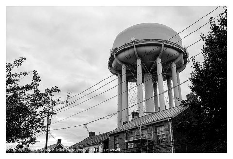 BW photograph of a water tower right of center overlooking some houses.