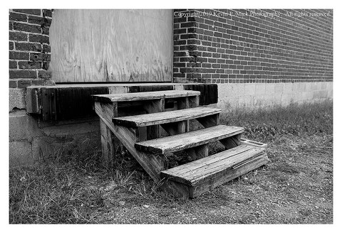 BW photograph of a set of old wooden stairs leading to a boarded-over entrance.