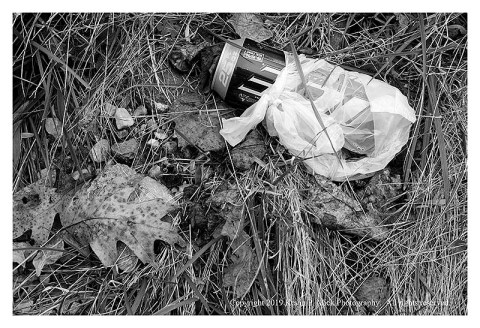 BW photograph of a can in a plastic bag laying next to a leaf.