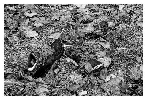 BW photograph of left behind shoes among leaves on the ground.