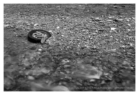 BW photograph of a tire laying in a stream.