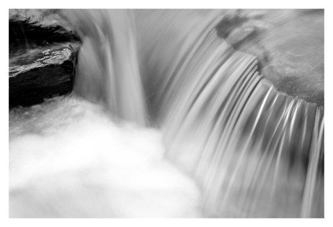 BW photograph of a small waterfall created by a large storm.