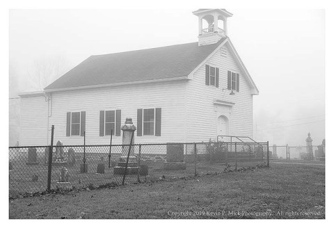 BW photograph of a church and cemetary enveloped in fog.