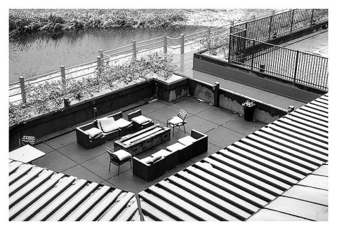 BW photograph of a hotel courtyard after a snow-looking down from a room window.