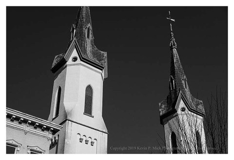 Bw photograph looling up at a pair of church steeples on a clear, sunny, day.