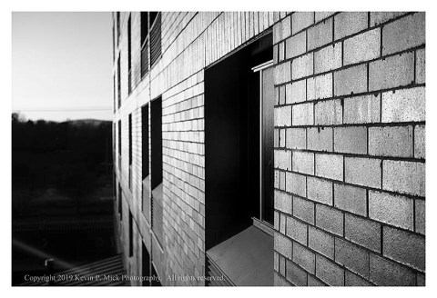 BW photograph of a sunlit hotel exterior wall looking out from a window.