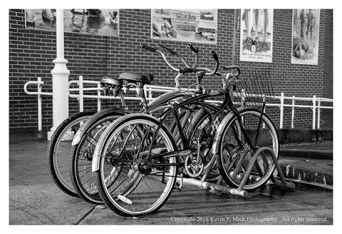 BW photograph of bikes parked on a boardwalk.