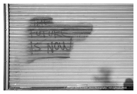 """BW photograph of """"The Future is Now"""" graffitti painted over on a closed shop door."""
