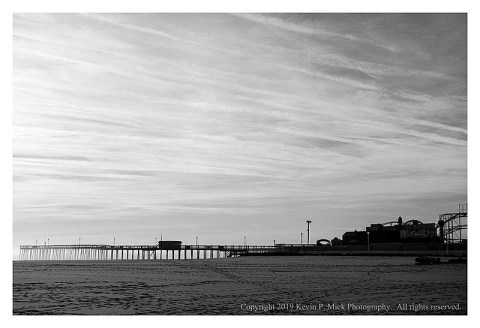 BW photograph of the Ocean City pier silhouetted against the morning sky.