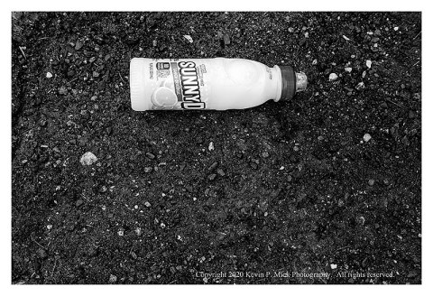 BW photograph of a discarded full Sunny D bottle of juice.