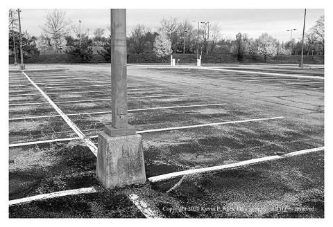 BW photograph of a light standard in an empty parking lot.