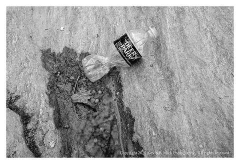 BW photograph of a twisted plastic bottle laying atop a rock.