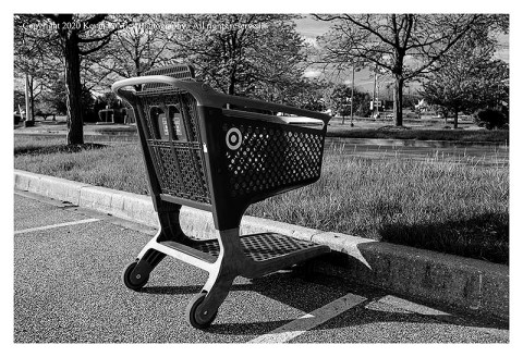 BW photograph of a single shopping cart parked on a curb.