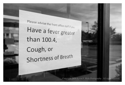 BW photograph of a COVID-19 symptom warning sign on a medical office window.