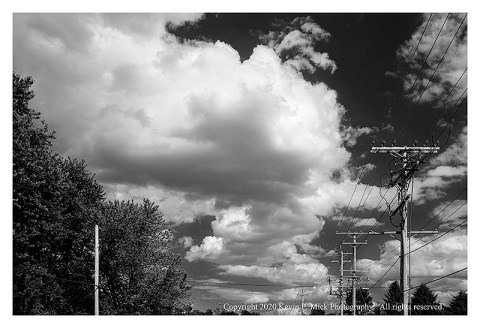 BW photograph of telephone poles and cumulous clouds.