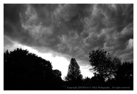 BW photograph of storm clouds over some trees.