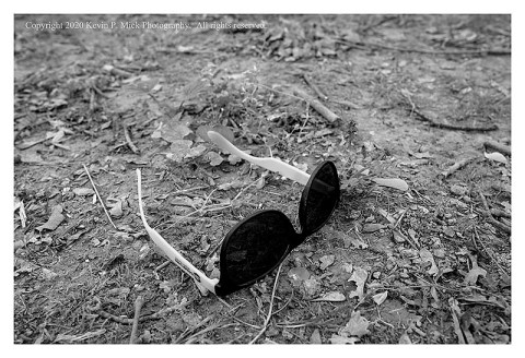 BW photograph of a pair of sunglasses left on the ground.