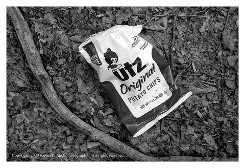 BW photograph of a small Utz potato chip bag left on the ground.