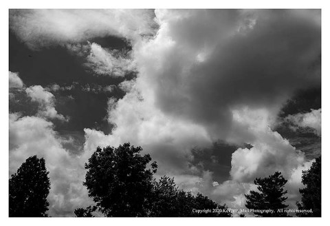BW photograph of a small plane flying into some large clouds.