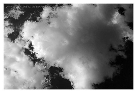 BW photograph looking up into a cloud formation.