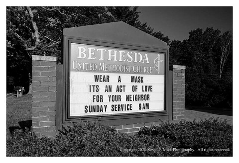 BW photograph of a church markee recommending the wearing of masks.