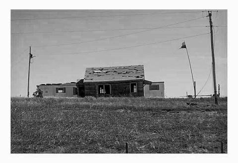 BW photograph of an upside down tattered American flag on the Pine Ridge Reservation.