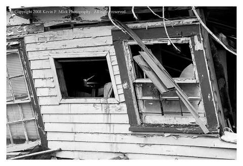 BW photograph of broken windows in a broken house three years after Hurricane Katrina.