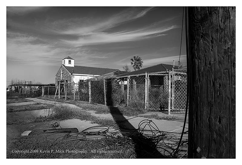 BW photograph of downed power lines near a church three years after Hurricane Katrina.