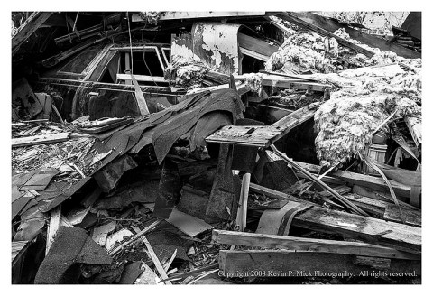 BW photograph of a car covered with roofing debris three years after Hurricane Katrina.