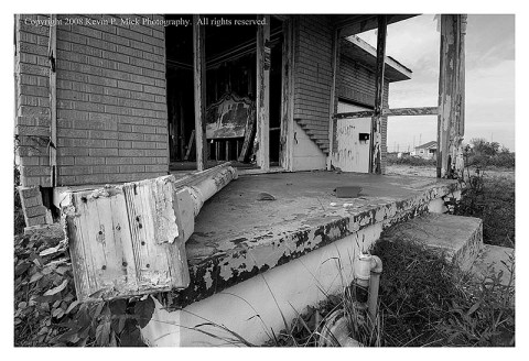 BW photograph of a headboard inside a gutted house three years after Hurricane Katrina.