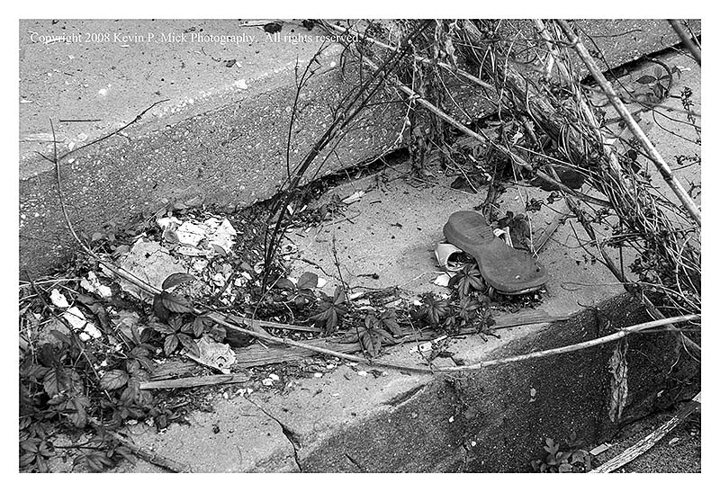 BW photograph of a sandal amid weeds on a step three years after Hurricane Katrina.